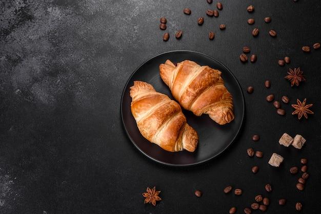 Świeży chrupiący pyszny francuski rogalik z ziaren kawy na czarnym stole