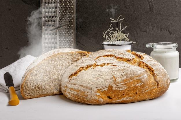 Świeży, ciepły, pieczony chleb rzemieślniczy na zakwasie z zakwasem na blacie kuchennym