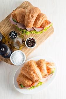 Świeży croissant lub kanapka z sałatką, baleron na drewnianym tle.