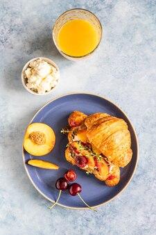 Świeży croissant z nektaryną z serka i wiśniowe śniadanie z croissantem i sokiem