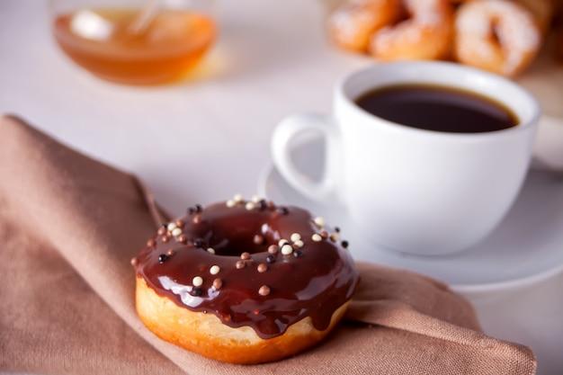 Świeży czekoladowy pączek z filiżanką kawy na stole