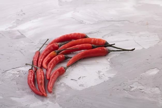 Świeży czerwony chili pojęcie na popielatym stole, kopii przestrzeń. nikt