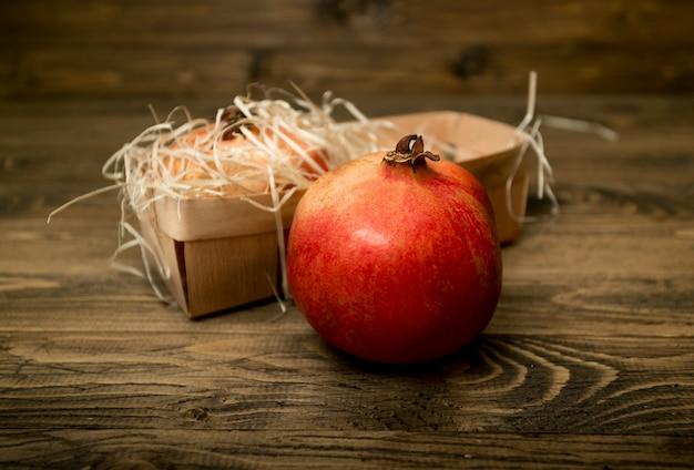 Świeży czerwony granat leżący na drewnianych deskach obok kosza