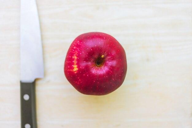 Świeży czerwony jabłko na drewnie z kuchennego noża odgórnym widokiem