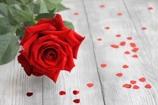 Świeży czerwony kwiat róży na drewnianej półce z czerwonymi konfetti serca. obraz walentynki.