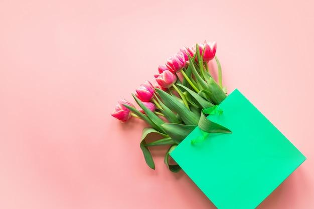 Świeży czerwony tulipan kwitnie w zielonej papierowej torbie na menchiach. wiosna.