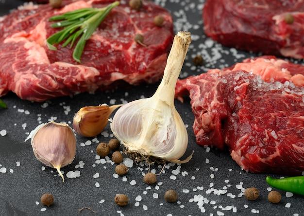 Świeży czosnek andraw kawałek wołowiny ribeye z rozmarynem, tymiankiem na czarnym stole, z bliska