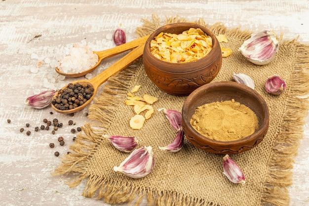 Świeży czosnek i jego produkty: suszone kawałki i proszek. naturalne składniki do gotowania zdrowej żywności. jasne drewniane tło, kopia przestrzeń