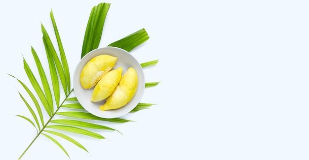 Świeży, dojrzały durian w białej płytce na liściach tropikalnych palm na białej powierzchni.
