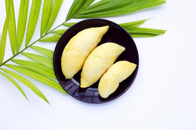 Świeży, dojrzały durian w talerzu na tropikalnych liściach palmowych na białej powierzchni.