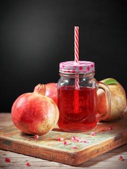 Świeży dojrzały granatowiec i szkła granatowa sok na starym drewnianym stole