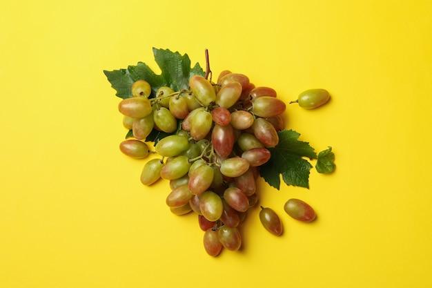 Świeży dojrzały winogrono na żółtym, widok z góry