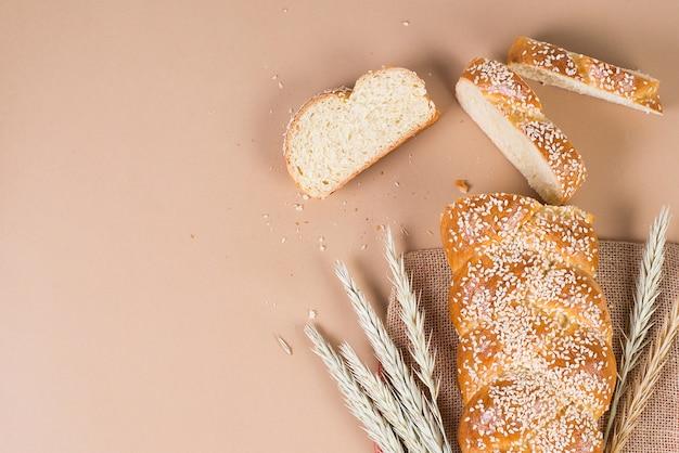 Świeży domowej roboty chleb z sezamowymi ziarnami przy piekarnią, modny pojęcie na pastelowej beż ścianie, odgórny widok, kopii przestrzeń