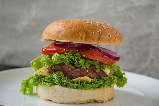 Świeży domowej roboty hamburger na białym talerzu.
