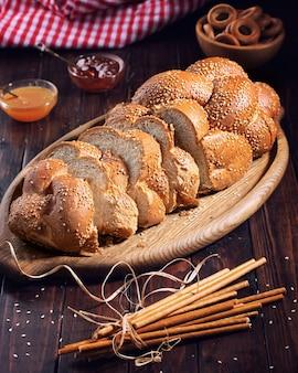 Świeży domowy biały chleb w plastrach umieszczonych na drewnianej desce do krojenia i drewnianym stole.