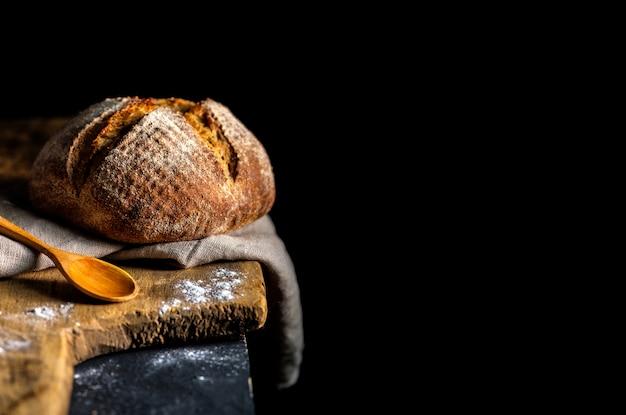 Świeży domowy chleb nad ciemnym stołem.