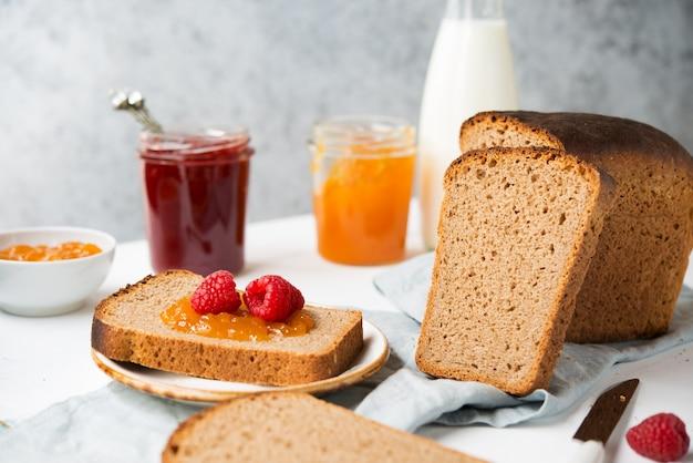 Świeży domowy chleb z dżemem i mlekiem, domowe proste jedzenie, jasne tło