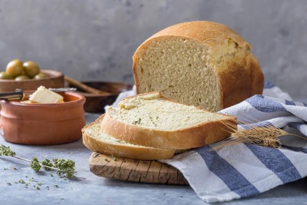 Świeży domowy chrupiący chleb i plasterki z oliwą z oliwek, masłem i zielonymi oliwkami, widok z góry. koncepcja pieczenia