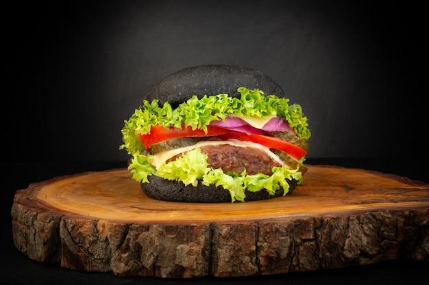 Świeży domowy czarny burger na drewnianej desce do krojenia