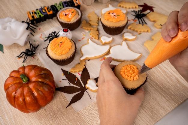 Świeży domowy deser na halloween z duchem, pełzającym pająkiem, nietoperzem, nawiedzonym zamkiem i przerażającą gałką oczną na drewnianym tle, kopia przestrzeń
