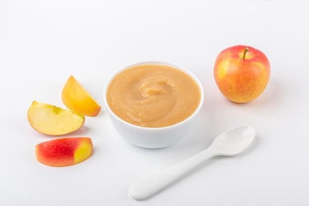 Świeży domowy mus jabłkowy. pojęcie właściwego odżywiania i zdrowego odżywiania. żywność ekologiczna i wegetariańska. biała miska z przecierem owocowym na tkaninie i pokrojonymi jabłkami na stole. jedzenie dla dzieci. skopiuj miejsce