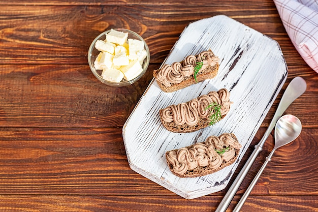 Świeży domowy pasztet z wątróbki drobiowej z marchewką, cebulą i masłem. przyozdobiony gałązką koperku. smarowane na chlebie. na drewnianym stole