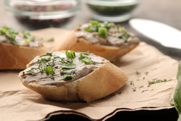 Świeży domowy pasztet z wątróbki drobiowej z zieleniną na chlebie na ciemnym tle. kanapka. zbliżenie