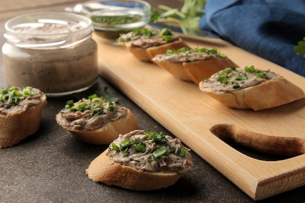 Świeży domowy pasztet z wątróbki drobiowej z zieleniną na chlebie na ciemnym tle. kanapka.