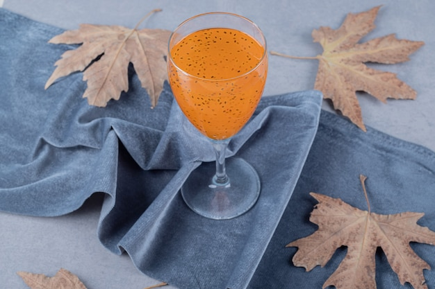 Świeży domowy sok owocowy z ozdobnymi liśćmi na szarej powierzchni