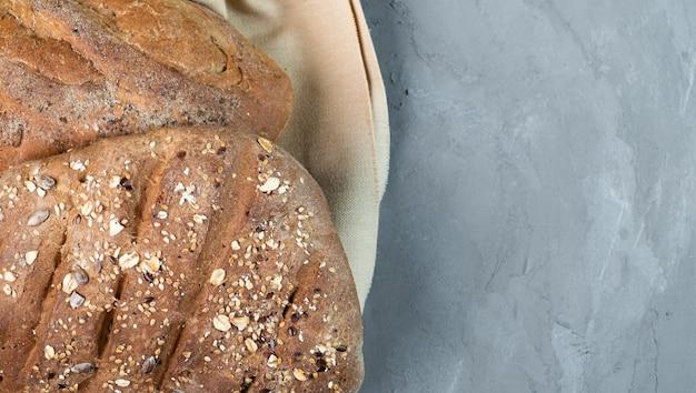 Świeży domowy zdrowy chleb na szarym tle, zbliżenie, widok z góry na szarym tle. chleb po lewej, wolne miejsce na tekst po prawej.