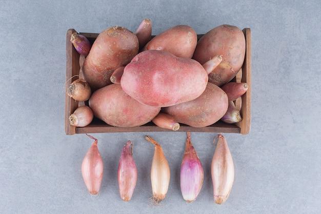 Świeży ekologiczny ziemniak i cebula na szarym tle.
