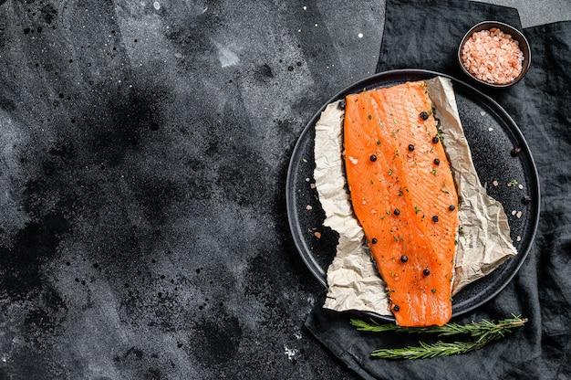 Świeży filet z łososia z solą, ziołami i przyprawami. czarne tło