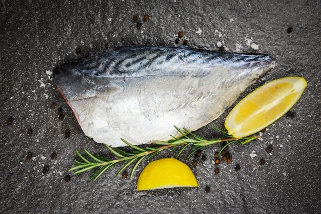 Świeży filet z ryby pokrojony na stek lub sałatkę z przyprawami ziołowymi rozmarynem i cytryną - surowe owoce morza na czarnym tle, longtail tuńczyk, wschodnie małe filety z tuńczyka do gotowania potraw