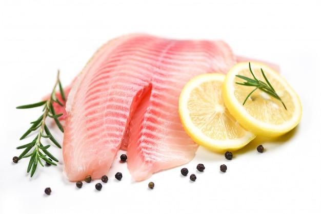 Świeży filet z ryby pokrojony na stek lub sałatkę z przyprawami ziołowymi rozmarynem i cytryną - surowy filet z ryby tilapia na białym tle i składniki do gotowania żywności