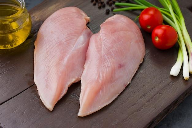 Świeży filet z surowego kurczaka bez skóry ułożony na drewnianej desce