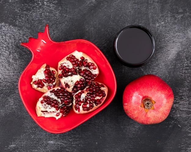 Świeży granat w czerwonym talerzu w kształcie granatu i sok z granatów na ciemno