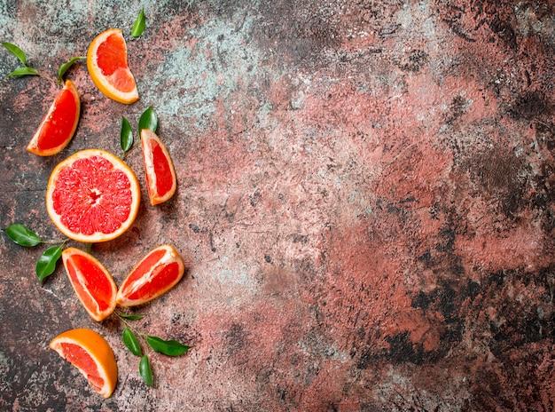 Świeży grejpfrut z liśćmi. na tle rustykalnym