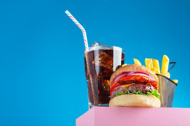 Świeży hamburger wołowy, cola i smażone frytki umieszczone na różowej podstawce i niebieskim tle. skopiuj miejsce na tekst, modny widok bohatera. orientacja pozioma