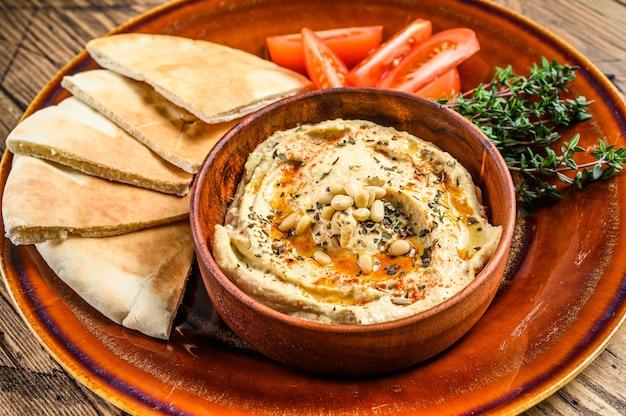 Świeży hummus z chlebem pita, pomidorem i pietruszką na rustykalnym talerzu.