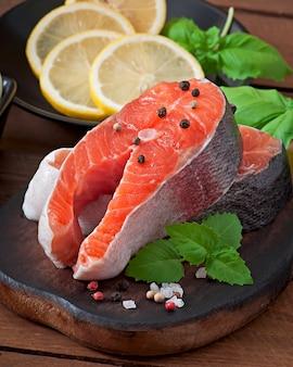 Świeży i surowy stek pstrąg na drewnianej desce do krojenia z plasterkami cytryny, rozmarynu i pieprzu