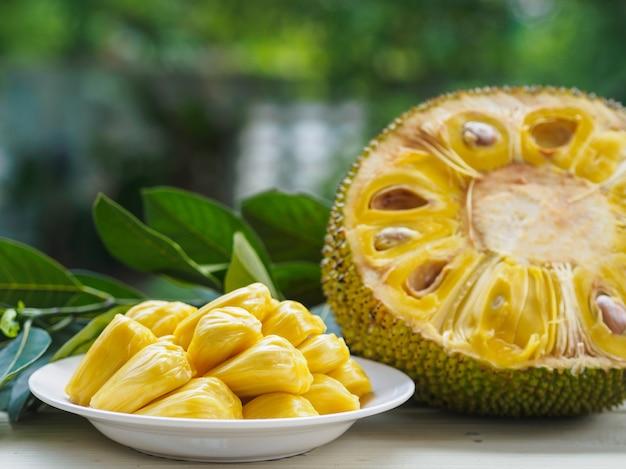 Świeży jackfruit w białym naczyniu, połówce dźwigarki owoc i jackfruit leaf na drewnianym stole ,.