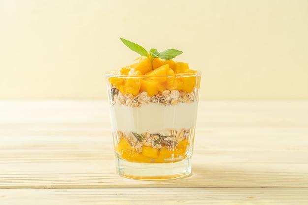 Świeży jogurt mango z muesli w szkle - styl zdrowej żywności