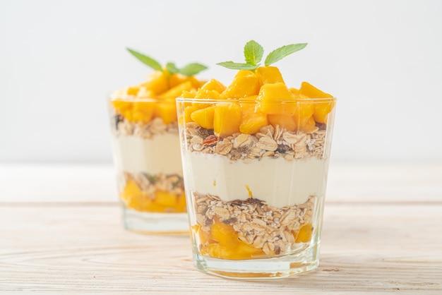 Świeży jogurt z mango z granolą w szklance - zdrowy styl jedzenia