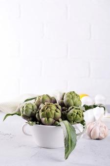 Świeży karczoch przygotowuje się do gotowania z czosnkiem, cytryną i oliwą z oliwek, wnętrze kuchni.