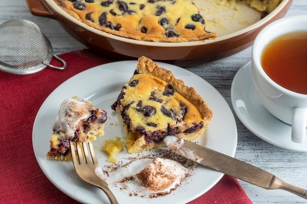 Świeży kawałek ciasta wiśniowego z lodami i biały kubek z herbatą na tle drewnianych, z bliska