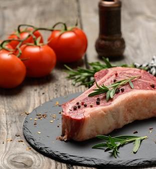 Świeży kawałek surowego mięsa wołowego, stek z rostbefu na drewnianej powierzchni, widok z góry