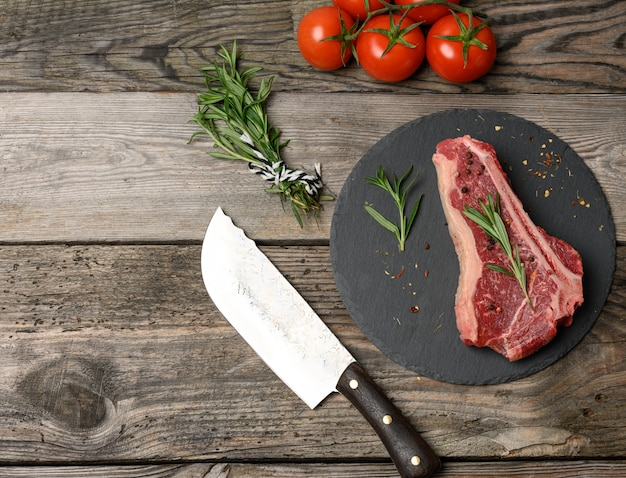 Świeży kawałek wołowiny, stek z rostbefu na czarnej desce z przyprawami, widok z góry