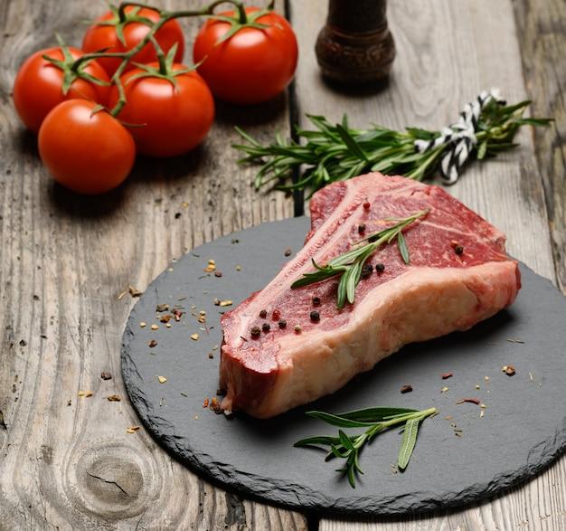 Świeży kawałek wołowiny, stek z rostbefu na czarnej tablicy z przyprawami, z bliska