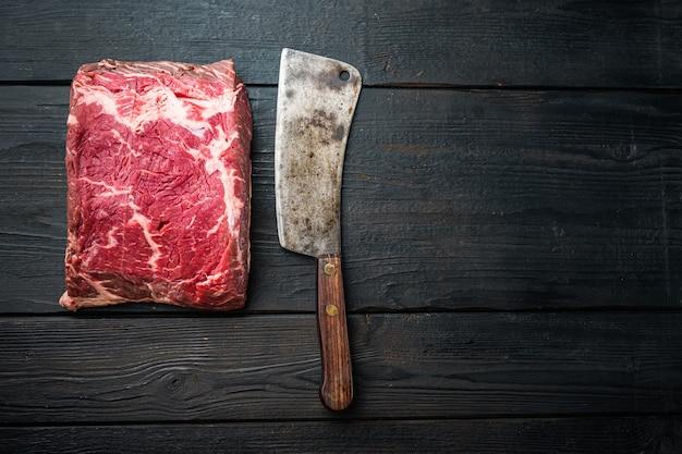Świeży klubowy surowy stek wołowy bez kości, na czarnym drewnianym stole