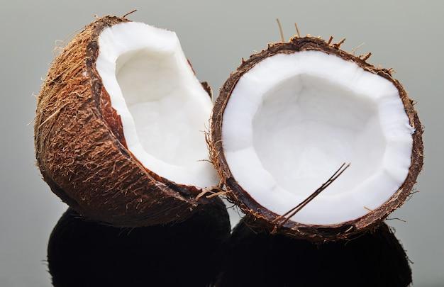 Świeży kokos posiekany na dwie połówki na szaro z odbiciem